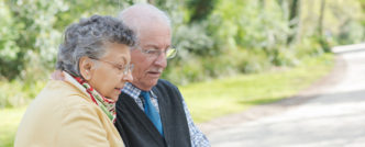 Elderly couple sat on bench looking at tablet