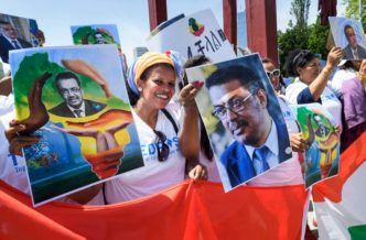 People hold placards picturing Ethiopian Candidate for the post of Director General of World Health Organization (WHO) Tedros Adhanom Ghebreyesus, during a rally on his support, in front of the United Nations offices, on May 23, 2017, in Geneva. The World Health Organization's 194 members on May 23, 2017 choose among three candidates to replace Margaret Chan as global health supremo, with each pledging to reform an agency under scrutiny. / AFP PHOTO / Fabrice COFFRINI